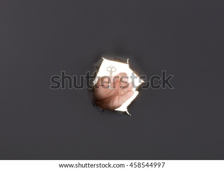 Male hand breaking through the gray paper background and holding key. High resolution.