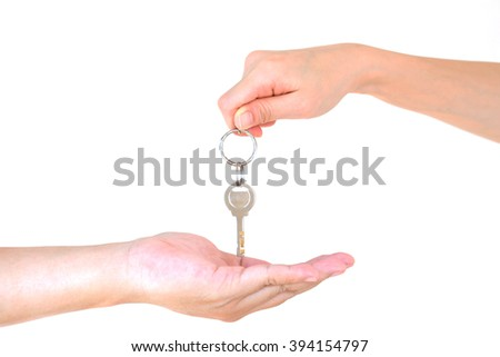 Male hand holding a key and handing it over to another person isolated