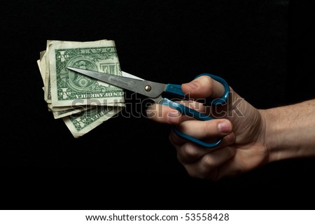 Male hand holding a pair of blue scissors cutting dollars, isolated on black background