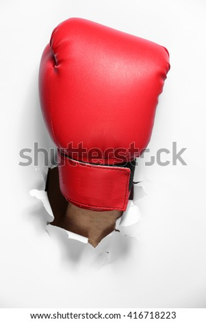 Male hand in boxing glove through white paper, isolated on white