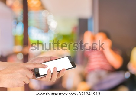 male hand is holding a modern touch screen phone and Coffee shop blur background with bokeh image.