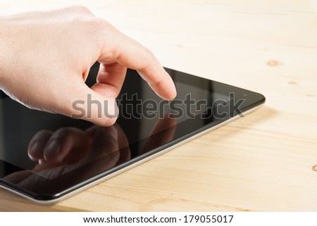 male hand is touching digital tablet pc on wood table with space for text