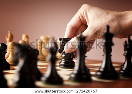 Male hand moving the black chess knight in focus in the middle of a game of chess