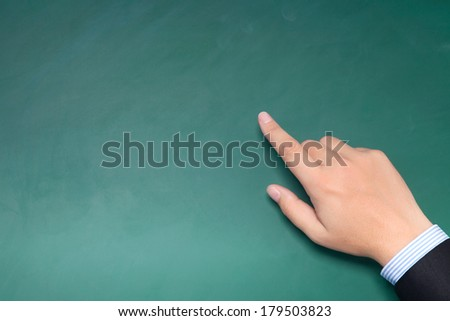male hand of businessman in a suit pointing to something on the green chalkboard