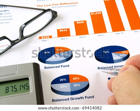 Male hand with pen on the investment chart with calculator and glasses