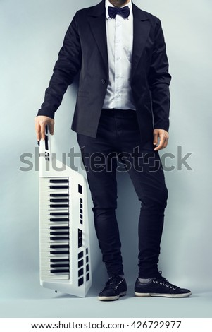 Male hands with synthesizer on light wall background