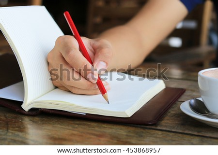 male hands writing in open notebook on table. selective focus.