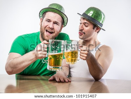 Male Irish friends in green hats toasting on St. Patrick's Day with large mugs of beer at bar tavern