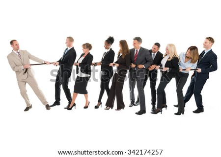 Male leader pulling business team while playing tug of war against white background