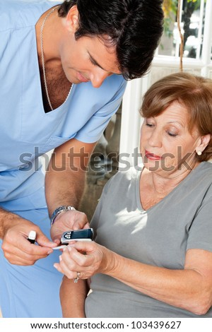 Male nurse measuring glucose level blood test using glucometer and sample strip