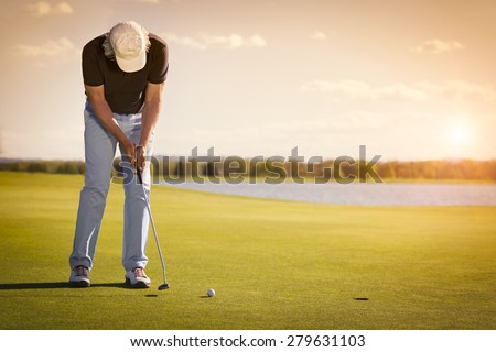 Male senior golf player putting on green at beautiful sunset, with empty copyspace.