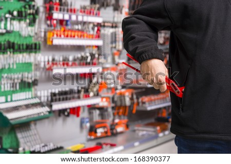 male shoplifter stealing tools in a hardware store