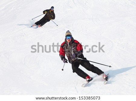 Male skier turning in deep powder with mountains valley's