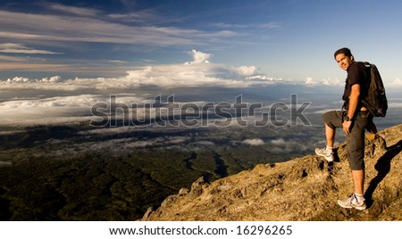 Male standing on top of mountain with fulfilled expression
