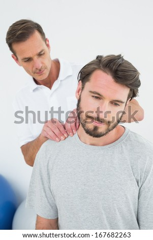 Male therapist massaging a content man's shoulders in the medical office