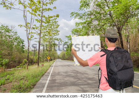 Male tourist with Back packer and hat standing and looking at road map,on road curve along with tropical forest.Concept forthcoming trip and Preparing for a safe journey.