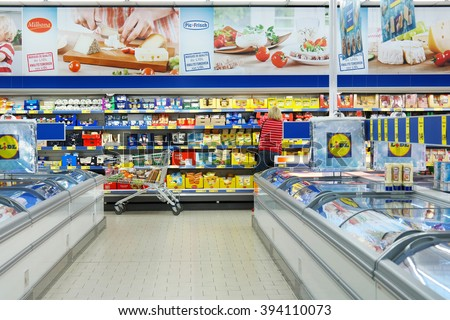 MALMEDY, BELGIUM - JULY 29, 2015: Interior of a Lidl supermarket. Shopper in the refrigerated fresh products aisle. Lidl is a German discount chain, 9800 stores, in 28 countries in Europe.