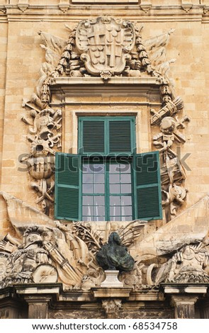 Malta La Valletta historical center intricately carved details and bronze bust on sandstone facade