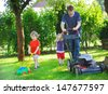 Man and two little sibling boys having fun with lawn mower in garden - stock photo
