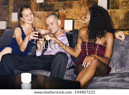 Man and two women toasting drinks on couch in bar