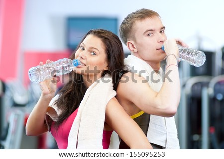 Man and woman drinking water after sport exercises. Fitness gym.