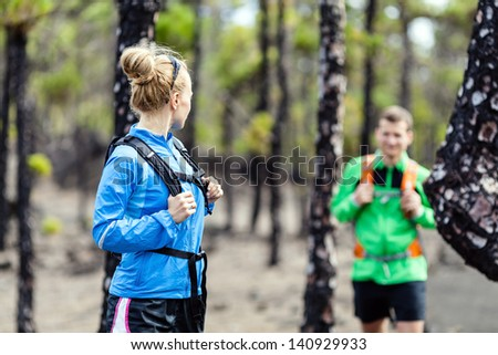 Man and woman hikers trekking on volcanic trail in mountains. Young couple hiking on La Palma, Canary Islands. Sport and exercising in summer nature outdoors.