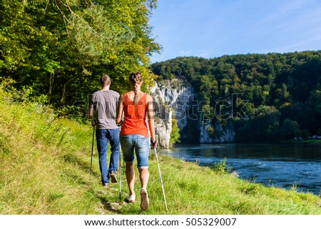 Man and woman hiking at river in summer for better fitness