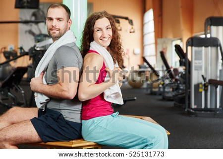 Man and woman taking a break during workout at the gym