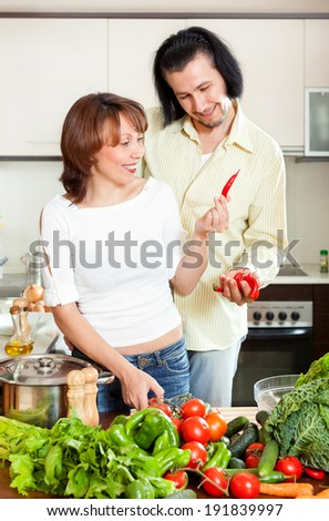 Man and woman with vegetables in kitchen