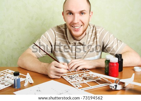 man assembling plastic airplane model and painting pieces, smiling, looking at camera