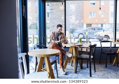 Man at Sitting in Coffee Shop and Using Tablet