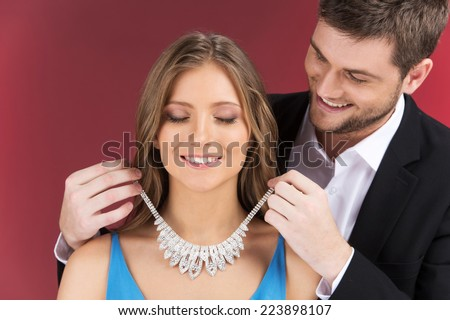 Man attaching necklace to girl's neck. man standing behind woman with eyes closed and jewelry