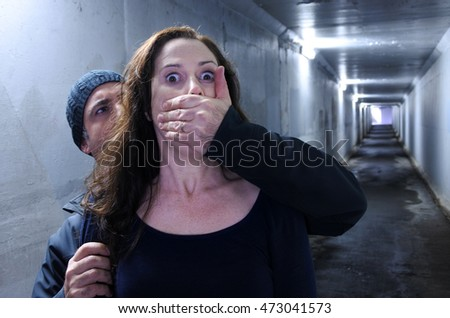 Man attacks a woman from behind in a  tunnel. Violence against women concept. Real people, copy space