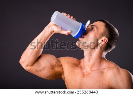 Man bodybuilder posing on gray background Man is holding a shaker for drinks. Man drinking a protein shake, water, amino acids from the shaker. Sports, sports nutrition, food additive.