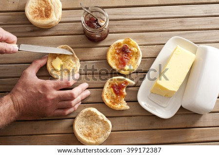 Man buttering a freshly toasted crumpet for breakfast, overhead view of his hands, the crumpets, jam and a pat of farm butter on a slatted wooden table