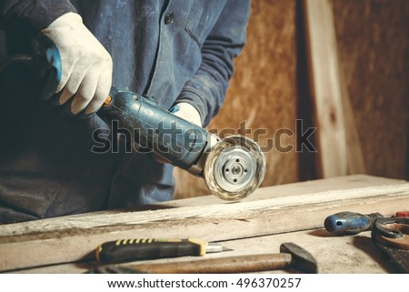Man carpenter mills the piece of wood by a grinding machine in his home workshop