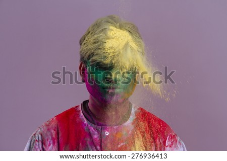 Man celebrating Holi festival with powder paints over colored background