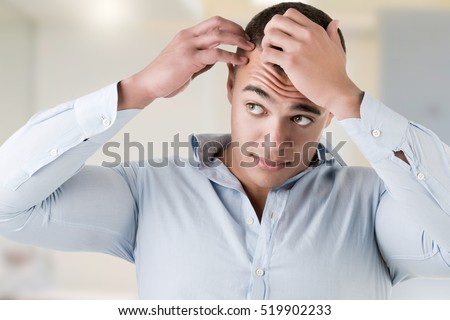 Man checking hairline, in a bathroom