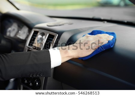 Man cleaning car dashboard, closeup