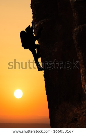 Man climbing on the rock on sunset background