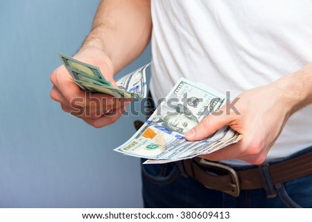 Man counting dollars. Young man with cash in his hands