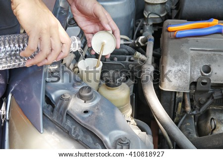 man doing car regular maintenance. hand pouring water from a clear bottle into a windshield wiper tank. another hand holding its cap.