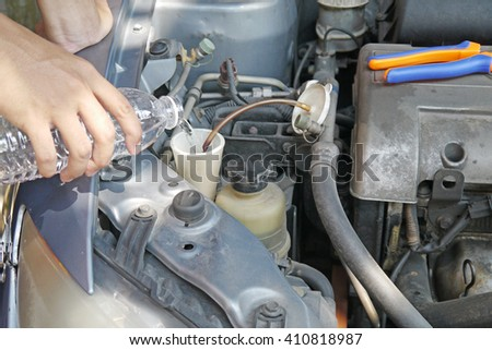 man doing car regular maintenance. hand pouring water from a clear bottle into a windshield wiper tank.partial view of other hand resting on car body.