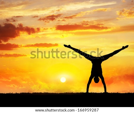man doing yoga handstand on the grass at sunset sky