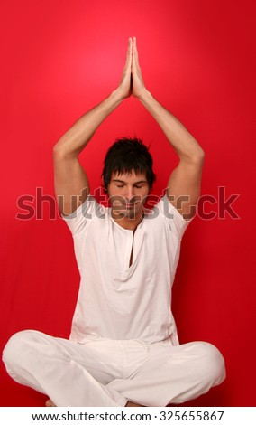 Man doing yoga, red background