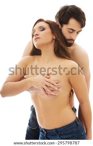 Man embracing woman and covering her breast.