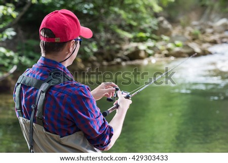 Man fisherman catching trout in the river fishing rod. Fly fishing in a forest creek in Europe. Professional sport angler catches a fish.