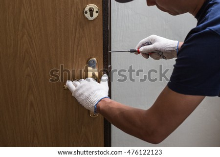 Man fixing the door with screwdriver