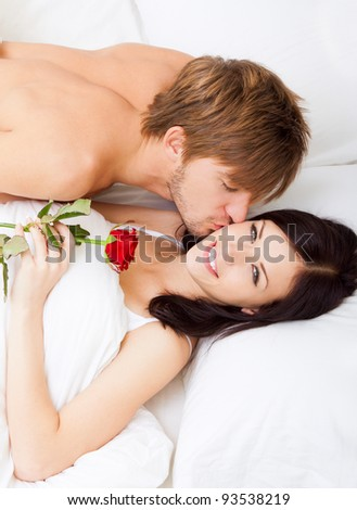 Man giving a rose and a kiss to his beautiful wife in bed, young lovely couple lying in a bed, happy smile love, girl looking at camera, top above view