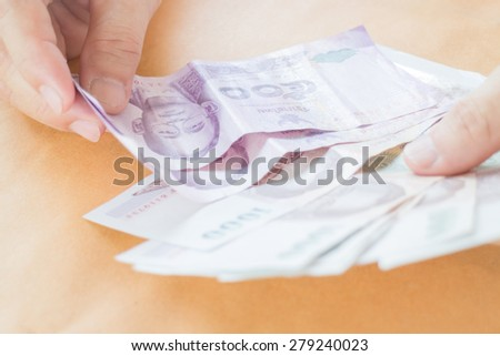 Man hand counting Thai baht banknote, stock photo